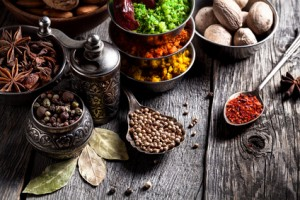 Spices, pepper grinder, spoon with seeds close up at grey wooden background