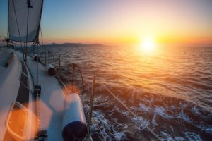 Luxery sailing yacht glides through the waves during a wonderful sunset.
